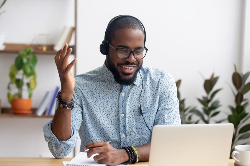 Smiling Trainer in headphones using laptop